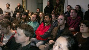 A packed room listens to the talks.
